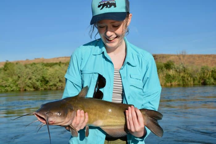 A woman in blue jacket holding catfish