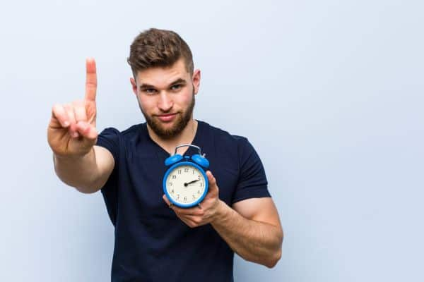 Man showing one finger with an alarm clock in his hand